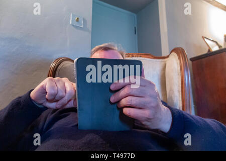 A man surfs the web with his tablet computer - Stock Image