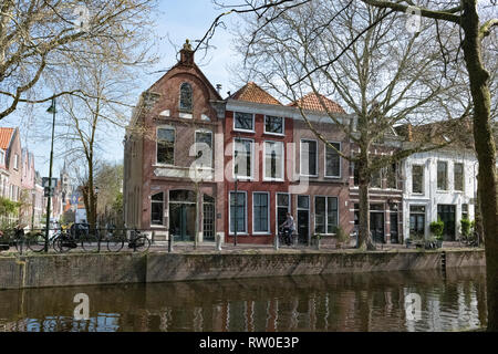 Netherlands, Gouda, 2017, cyclist passing in front of traditional houses on the banks of a canel. - Stock Image