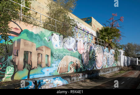 A boundary wall covered with colourful street art, Seville, Spain. - Stock Image