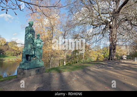 Ørstedsparken, the Ørsted Park, in autumn colours. Bronze statue of Natalie Zahle, Danish reform pedagogue and pioneer on women's education in Denmark - Stock Image