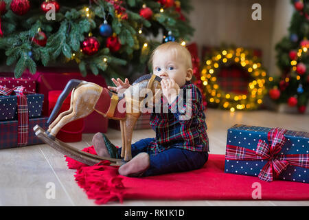 Christmas portrait of cute little newborn baby boy, dressed in christmas clothes and wearing santa hat, studio shot, winter time. - Stock Image