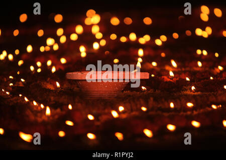 A Diwali earthen lamp kept in the center of marigold flowers and other small candles during a Hindu religious ritual, during Diwali festival in India. - Stock Image