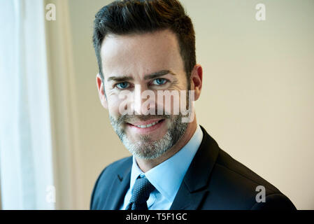 Close-up of smiling businessman standing in hotel - Stock Image