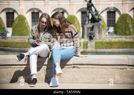 Two young women sitting near the fountain and looking at the phone screen. Mid shot - Stock Image