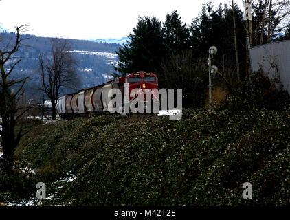 Freight train approaching railbridge over Fraser River, British Columbia - Stock Image