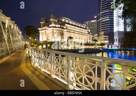 Cavenagh bridge Fullerton Hotel Skyline of Singapore  South East Asia twilight - Stock Image
