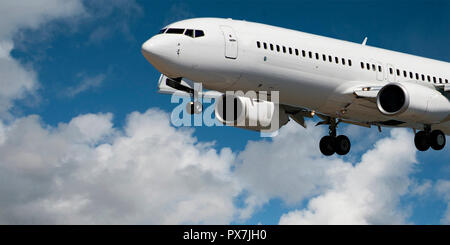 Very closeup view of a commercial passenger jet aircraft flyng in a blue sky, with white coloured wispy cumulus clouds. On approach to Sydney,Australi. - Stock Image