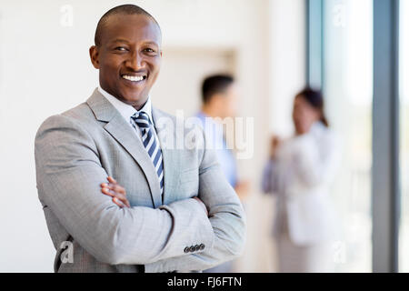successful African business man with arms folded in modern office - Stock Image