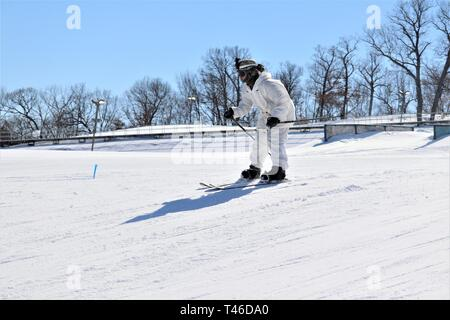 A student in the Fort McCoy Cold-Weather Operations Course (CWOC) Class 19-05 practices skiing March 11, 2019, at Whitetail Ridge Ski Area at Fort McCoy, Wis. In addition to skiing, CWOC students are trained on a variety of cold-weather subjects, including snowshoe training as well as how to use ahkio sleds and other gear. Training also focuses on terrain and weather analysis, risk management, cold-weather clothing, developing winter fighting positions in the field, camouflage and concealment, and numerous other areas that are important to know in order to survive and operate in a cold-weather - Stock Image