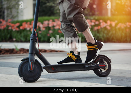 Close up of man riding black electric kick scooter at beautiful park landscape. Man is on foreground, modern building and park is on background. - Stock Image