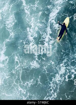 A surfer paddles out. Manhattan Beach, California USA. - Stock Image