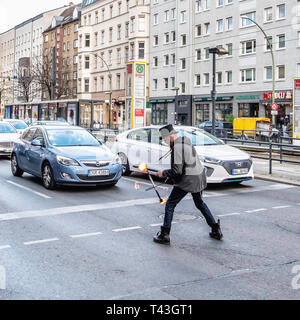 Berlin Mitte. Juggler juggles with fire in the middle of the busy Rosenthaerplatz intersection - Stock Image