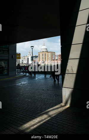 The dome of St Paul's Cathedral seen from a dark underpass on the Southbank in London. - Stock Image