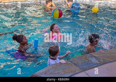 girls, boys, children, splashing one another, splashing water, freshwater swimming pool, pool party, Castro Valley, Alameda County, California - Stock Image