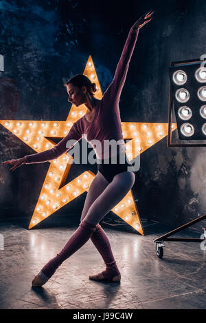 Ballet dancer practice exercise in front of a illuminated star on a dak studio - Stock Image