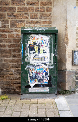 Advertising posters and flyers on a British Telecom cable junction box - Stock Image