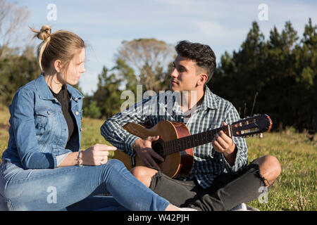 man and woman playing guitar on a picnic blanket under a sunny afternoon - Stock Image