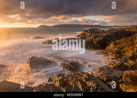 Golden evening light bathes the rocky shores near Constantine Bay in North Cornwall, England. Summer (July) 2017. - Stock Image