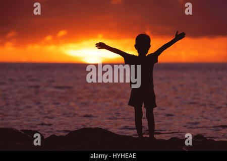 Childhood concept with happy child at sunset beach - Stock Image