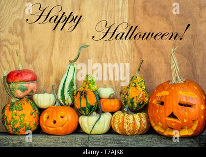 Happy Halloween copy space with carved pumpkins and gourds at the bottom against wooden background in side view - Stock Image