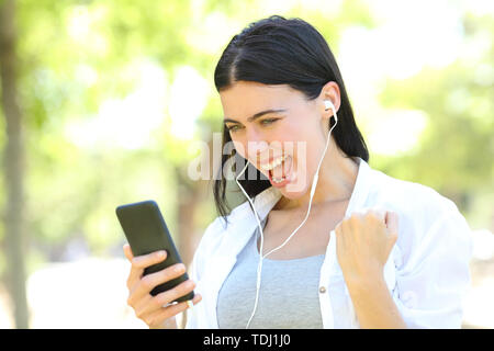 Excited woman wearing earphones finding online music offers on smart phone standing in a park - Stock Image