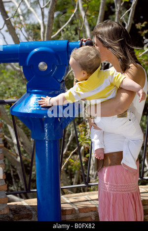 Mother holding toddler looking though telescope at a viewpoint in Mijas Pueblo, Costa del Sol, Andalucia, Spain - Stock Image