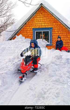 A little boy (6 yrs old) on a sledge sledging down from the top of a house in very deep snow in Quebec. Winter 2018-2019 saw very heavy snowfall. - Stock Image
