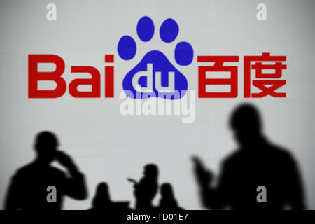 The Baidu logo is seen on an LED screen in the background while a silhouetted person uses a smartphone in the foreground (Editorial use only) - Stock Image