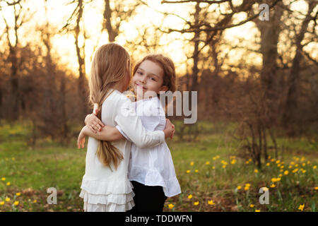 Best friends happy to meet you. Girls in white dresses cuddling in spring meadow. Family bonds - Stock Image