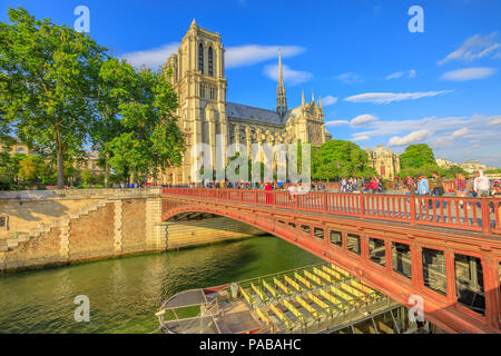 Paris, France - July 1, 2017: empty Bateaux-Mouches docked on the Seine under the red bridge with Notre Dame Cathedral on the Ile de la Cite in a sunny day and blue sky on background. - Stock Image