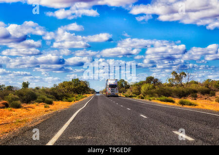 Remote empty road Castlereagh highway B55 in rural outback part of NSW, Australia with lonely distant road train truck transporting cargo shipment. - Stock Image