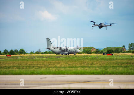 Drone flying in airport area near plane in violation of restrictions for unmanned aircraft and drones - Stock Image