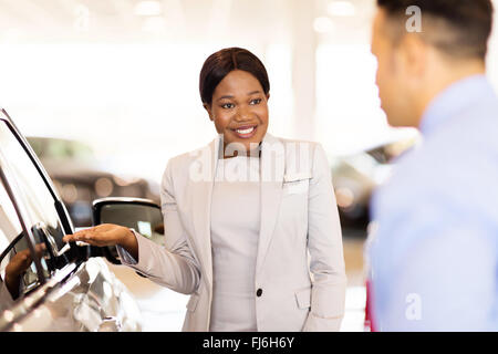 professional African saleswoman selling car to a customer in showroom - Stock Image