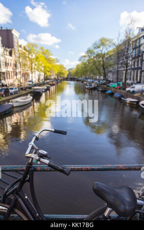 View of bicycle and canal, central Amsterdam, The Netherlands - Stock Image