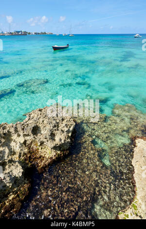 Rocky coastline in Cayman Islands with fishing boat in the transparent blue water. - Stock Image