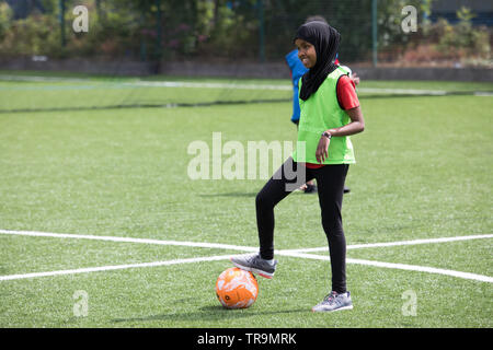 Muslim girl playing football on an astroturf training pitch. Wearing hijab (headscarves). - Stock Image