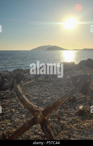 Anchor Left on Beach with Sun low on the Horizon, Saronida, East Attica, Greece. - Stock Image