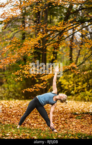 Young woman stretching outdoors - Stock Image