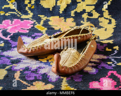 Opanci, traditional leather folk shoes, a part of the Serbian national costume, are lying on a kilim, a traditional handmade flat-woven floor rug. - Stock Image