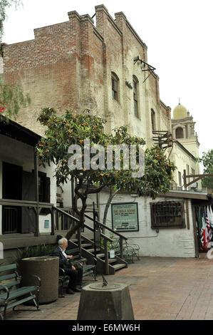 Elderly man sitting outside Avila Adobe house, Calle Olvera, or Olvera Street. El Pueblo de Los Angeles Historic - Stock Image