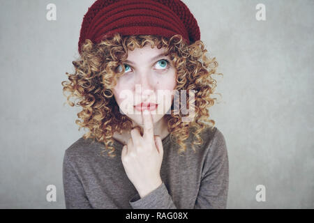 Close-up portrait of a beautiful and young funny thoughtful woman with blue eyes and curly blonde hair thinking and wearing a red woolen cap - Stock Image