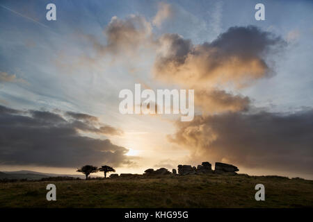 Combestone Tor on Dartmoor silhouetted against a dramatic sky at sunrise - Stock Image