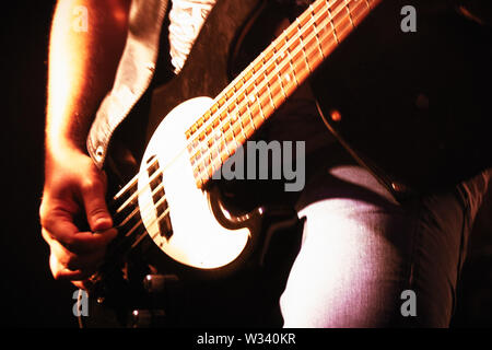 Bass guitarist on stage playing bass guitar close-up. Blurred image - Stock Image