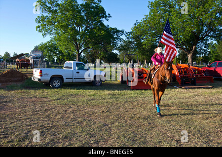 Cowgirl  waving flag in stockyard before opening ceremony of PRCA rodeo event in Texas, USA - Stock Image