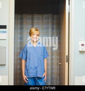 Doctor in scrubs standing in doorway, smiling - Stock Image