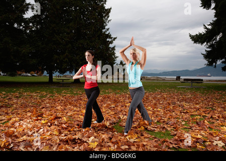 Two young women doing yoga at Spanish Bank in Vancouver, British Columbia, Canada - Stock Image