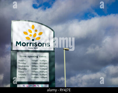 Morrisions high street  supermarket store sign against stormy skies - Stock Image