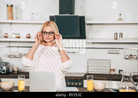 attractive woman touching eye glasses while standing near glasses with orange juice and laptop - Stock Image
