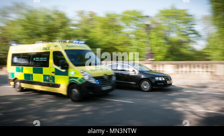Emergency ambulance overtaking a car in traffic - Stock Image