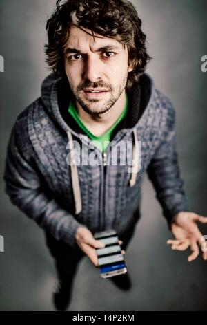 Young man with smartphone in hand, looks questioning, annoyed into camera, studio shot, Germany - Stock Image